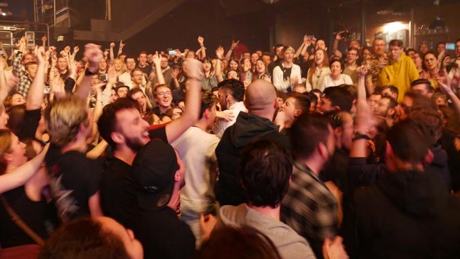 Le public d'un concert pop-rock en train de chanter et danser